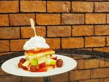 薄煎饼用新鲜水果和打好的奶油在玻璃桌上与 免版税库存图片