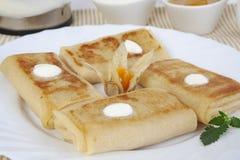 薄煎饼用茶的酸奶干酪用蜂蜜、酸性稀奶油和柠檬 免版税库存图片