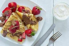 薄煎饼用草莓下了毛毛雨用巧克力 在白色木背景 顶视图 免版税图库摄影