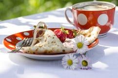 薄煎饼用草莓和酸性稀奶油。在三朵雏菊附近 免版税库存图片