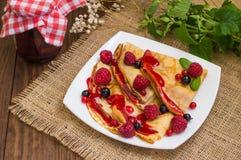 薄煎饼用莓、无核小葡萄干、糖和薄菏 木背景 顶视图 特写镜头 库存图片