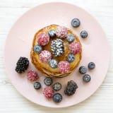 薄煎饼用莓果、蜂蜜和糖在一块桃红色板材在一张白色木桌上,顶上的看法 平的位置,顶视图,从上面 克洛 免版税库存图片
