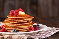 薄煎饼用莓果和枫蜜在盘在纺织品餐巾 免版税库存图片