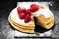 薄煎饼用莓果和糖在黑暗的背景 免版税库存照片