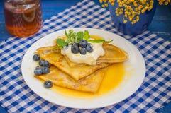 薄煎饼用蓝莓、打好的奶油和薄荷的香蜂草小树枝  木蓝色背景 特写镜头 库存图片