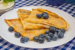 薄煎饼用蓝莓、打好的奶油和薄荷的香蜂草小树枝  木蓝色背景 特写镜头 库存照片