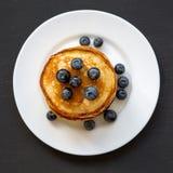 薄煎饼用蓝莓和蜂蜜在白色板材在黑暗的木桌,顶上的看法上 平的位置,顶视图 库存照片