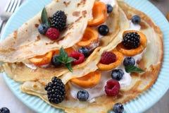薄煎饼用蓝莓和蜂蜜,健康早午餐 薄煎饼用在酸性稀奶油的莓果 免版税库存图片
