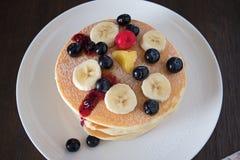 薄煎饼用蓝莓和香蕉在白色板材 免版税库存照片