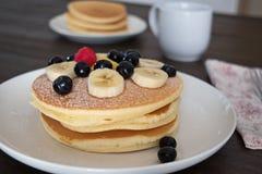 薄煎饼用蓝莓和香蕉在白色板材 免版税图库摄影