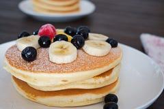 薄煎饼用蓝莓和香蕉在白色板材 库存图片