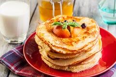 薄煎饼用蜂蜜、果子和杯牛奶 免版税库存图片