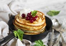 薄煎饼用蜂蜜、酸性稀奶油和红浆果在葡萄酒scourage 库存照片