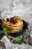 薄煎饼用蜂蜜、酸性稀奶油和红浆果在葡萄酒scourage 库存图片