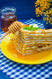 薄煎饼用蜂蜜、黄油和薄荷的香蜂草小树枝  木蓝色背景 特写镜头 免版税库存照片
