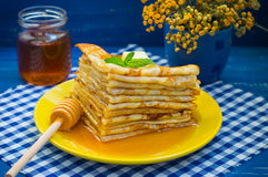 薄煎饼用蜂蜜、黄油和薄荷的香蜂草小树枝  木蓝色背景 特写镜头 免版税库存图片