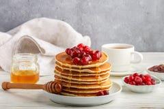 薄煎饼用蜂蜜和新鲜的莓果 蔓越桔,越橘 免版税库存图片