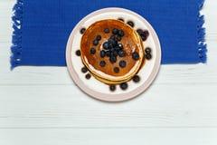 薄煎饼用蜂蜜和蓝莓在一块蓝色餐巾 免版税库存图片
