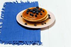 薄煎饼用蜂蜜和蓝莓在一块蓝色餐巾 库存照片