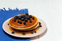 薄煎饼用蜂蜜和蓝莓在一块蓝色餐巾 图库摄影
