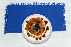 薄煎饼用蜂蜜和蓝莓在一块蓝色餐巾 库存图片