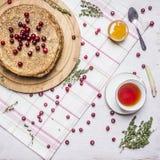 薄煎饼用蜂蜜和蔓越桔、一杯茶用麝香草和在切板的一把匙子在木土气backgroun的一块餐巾 免版税库存图片