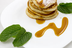 薄煎饼用蜂蜜和薄荷叶 免版税库存照片