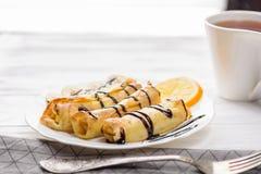 薄煎饼用香蕉,打好的奶油装饰用在白色木背景的巧克力糖浆 并且一杯茶 库存图片