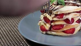 薄煎饼的部分的英尺长度装饰用在说谎在桌和人上的板材的草莓采取和平它与f 影视素材
