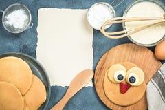 薄煎饼的食谱与孩子的滑稽的面孔 库存图片