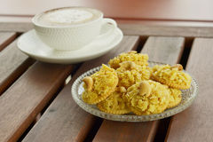薄脆饼干冠上了玉米片和热的热奶咖啡咖啡在木桌上 免版税库存照片