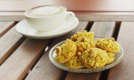 薄脆饼干冠上了玉米片和热的热奶咖啡咖啡在木桌上 免版税图库摄影