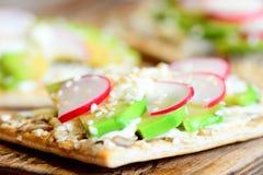 薄脆饼干开胃菜用调味汁和菜 在酥脆薄脆饼干的鲕梨和萝卜切片与在木板的种子 免版税库存照片