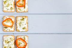 薄脆饼干用乳脂干酪、甜椒、种子和绿色 在灰色桌上的开胃菜 健康快餐,顶视图,平的位置 免版税库存照片