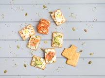 薄脆饼干用乳脂干酪和各种各样的顶部 在灰色桌上的开胃菜 健康快餐,顶视图,平的位置 免版税库存图片