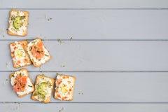 薄脆饼干用乳脂干酪和各种各样的顶部 在灰色桌上的开胃菜 健康快餐,顶视图,平的位置 库存图片