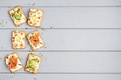 薄脆饼干用乳脂干酪和各种各样的顶部 在灰色桌上的开胃菜 健康快餐,顶视图,平的位置 库存照片