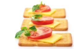 薄脆饼干用干酪、蕃茄和蓬蒿 库存照片