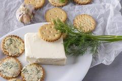 薄脆饼干用被抹上的大蒜黄油用在一块白色板材的莳萝 免版税库存图片