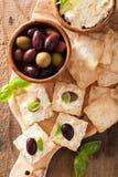 薄脆饼干用软干酪和橄榄 开胃菜干酪新鲜的被磨碎的健康蕃茄 库存图片