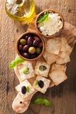 薄脆饼干用软干酪和橄榄 开胃菜干酪新鲜的被磨碎的健康蕃茄 库存照片