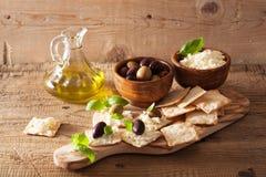 薄脆饼干用软干酪和橄榄 开胃菜干酪新鲜的被磨碎的健康蕃茄 免版税图库摄影