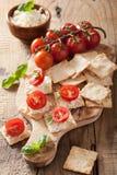 薄脆饼干用软干酪和蕃茄 开胃菜干酪新鲜的被磨碎的健康蕃茄 免版税库存照片