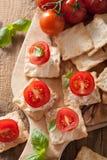 薄脆饼干用软干酪和蕃茄 开胃菜干酪新鲜的被磨碎的健康蕃茄 免版税图库摄影