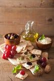 薄脆饼干用软干酪橄榄葡萄 开胃菜干酪新鲜的被磨碎的健康蕃茄 免版税图库摄影