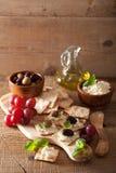 薄脆饼干用软干酪橄榄葡萄 开胃菜干酪新鲜的被磨碎的健康蕃茄 库存照片