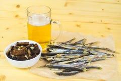 薄脆饼干,一个杯子低度黄啤酒,在桌上的干鱼 库存图片
