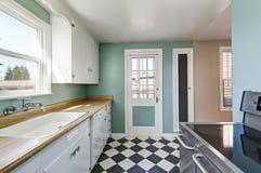 薄荷的墙壁和白色和黑角规铺磁砖了厨房地板 库存照片