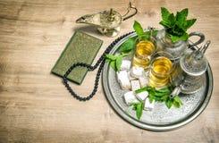 薄荷的茶、欢欣、阿拉伯灯笼、圣经古兰经和念珠 库存图片