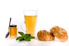 薄荷的茶用蜂蜜和新鲜的谄媚新月形面包 免版税库存图片